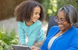 Image of happy grandmother and granddaughter enjoying HughesNet satellite Internet service on tablet