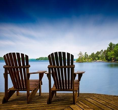 Adirondack chairs on lake-side deck